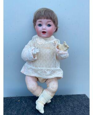 Bambola bebe'caractère con testa in bisquit, occhi mobili e corpo in cartapesta.Firma Kammer e Reinhardt.Germania