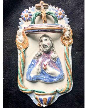 Acquasantiera in maiolica con motivi floreale, putti in rilievo e figura di Cristo al centro.Manifattura di Grottaglie,Puglia.