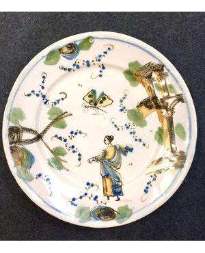 Piatto in maiolica decorato con figura femminile,ambiente rupestre e insetti.Manifattura Guidobono,Savona.