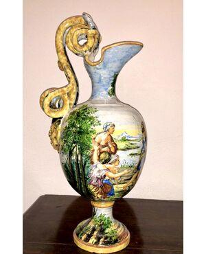 Versatoio in maiolica con manico a serpenti e mascherone e scena istoriata con il mito di Dafne.Manifattura di Angelo Minghetti,Bologna.