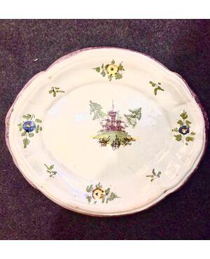 Piatto ovale in maiolica a gran fuoco con decoro floreale e architettonico.Manifattura Ferniani,Faenza.
